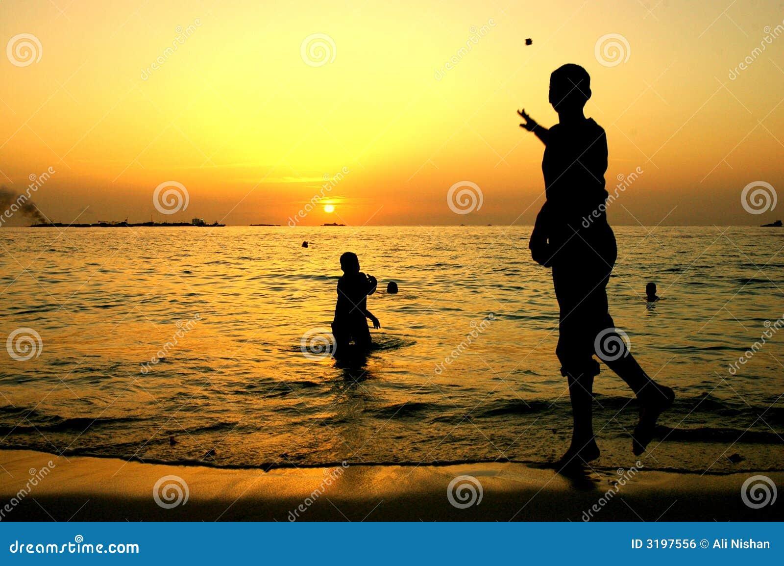 Crianças que jogam quando pores do sol