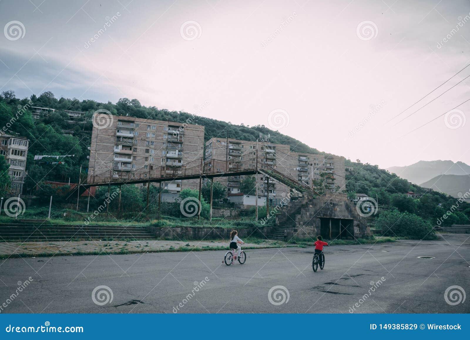 Crian?as que montam bicicletas no parque de uma cidade suburbana