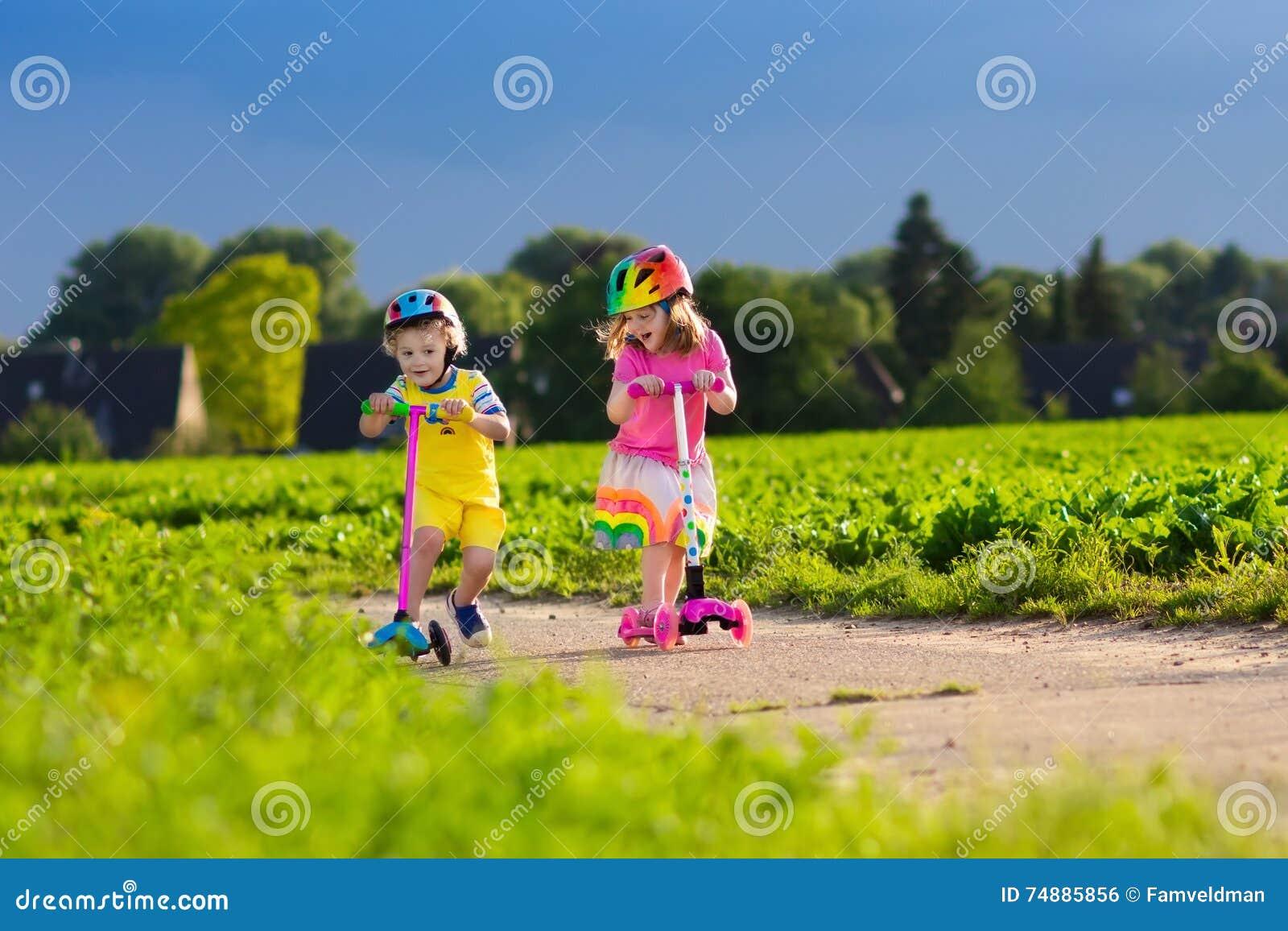 Crianças que montam o  trotinette  no dia de verão ensolarado