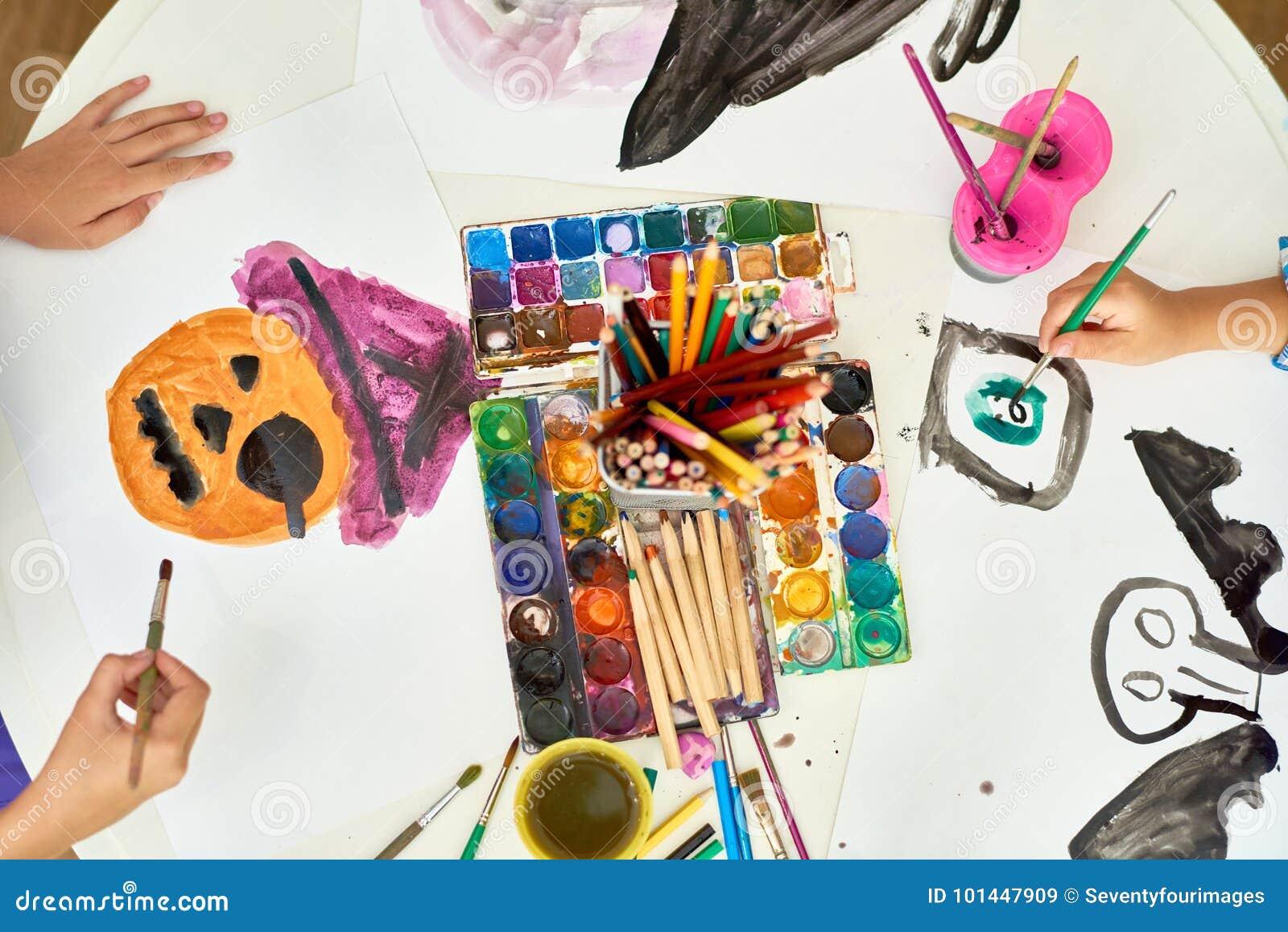 Crianças que pintam imagens de Dia das Bruxas em Art Class