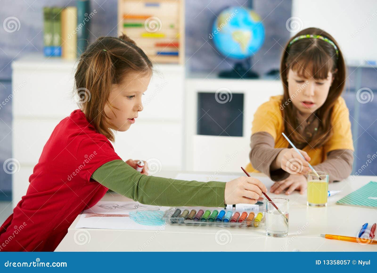Crianças que pintam na classe de arte
