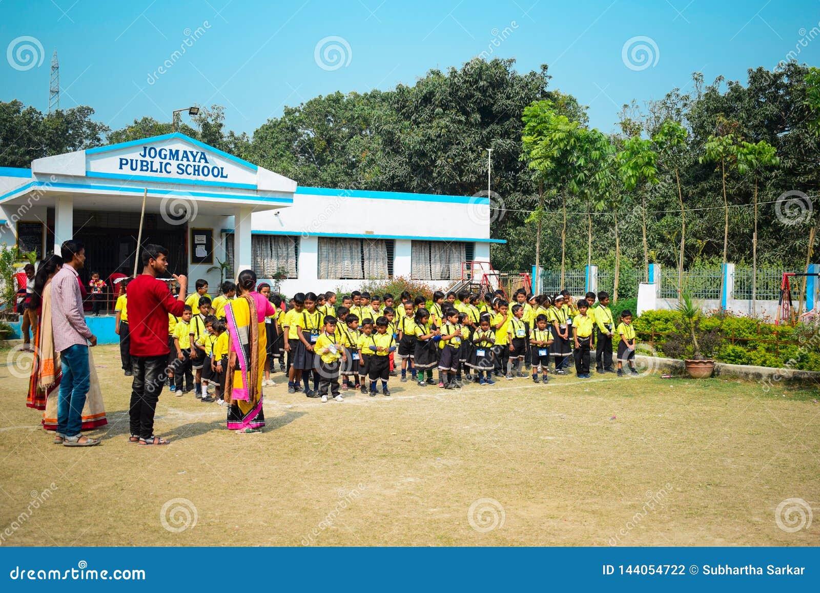 Crianças que rezam o hino nacional antes dos começos da escola no uniforme na frente do prédio da escola com os professores