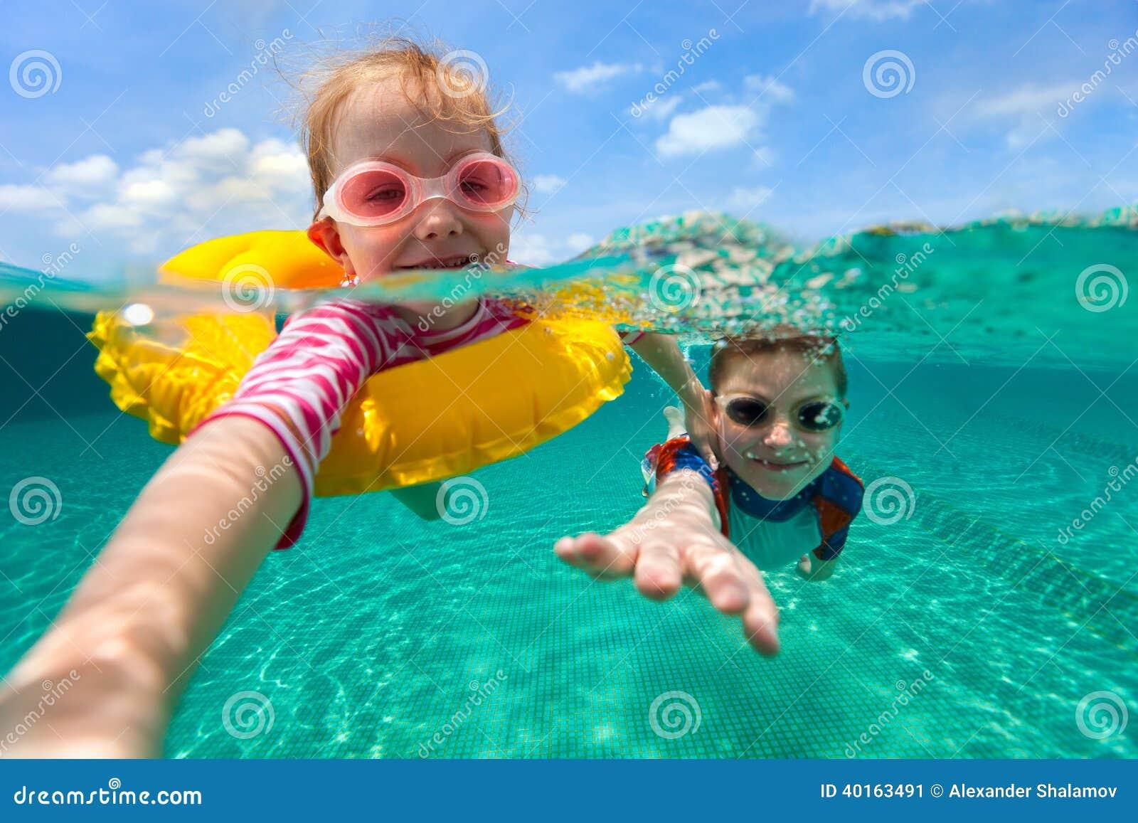 Crianças que têm a natação do divertimento em férias de verão