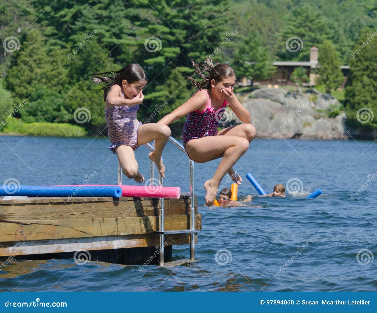 Crianças que têm o divertimento do verão que salta fora da doca no lago