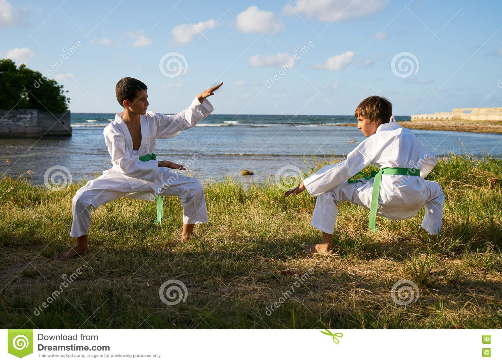 Crianças que treinam na escola do karaté para o divertimento do lazer da atividade do esporte