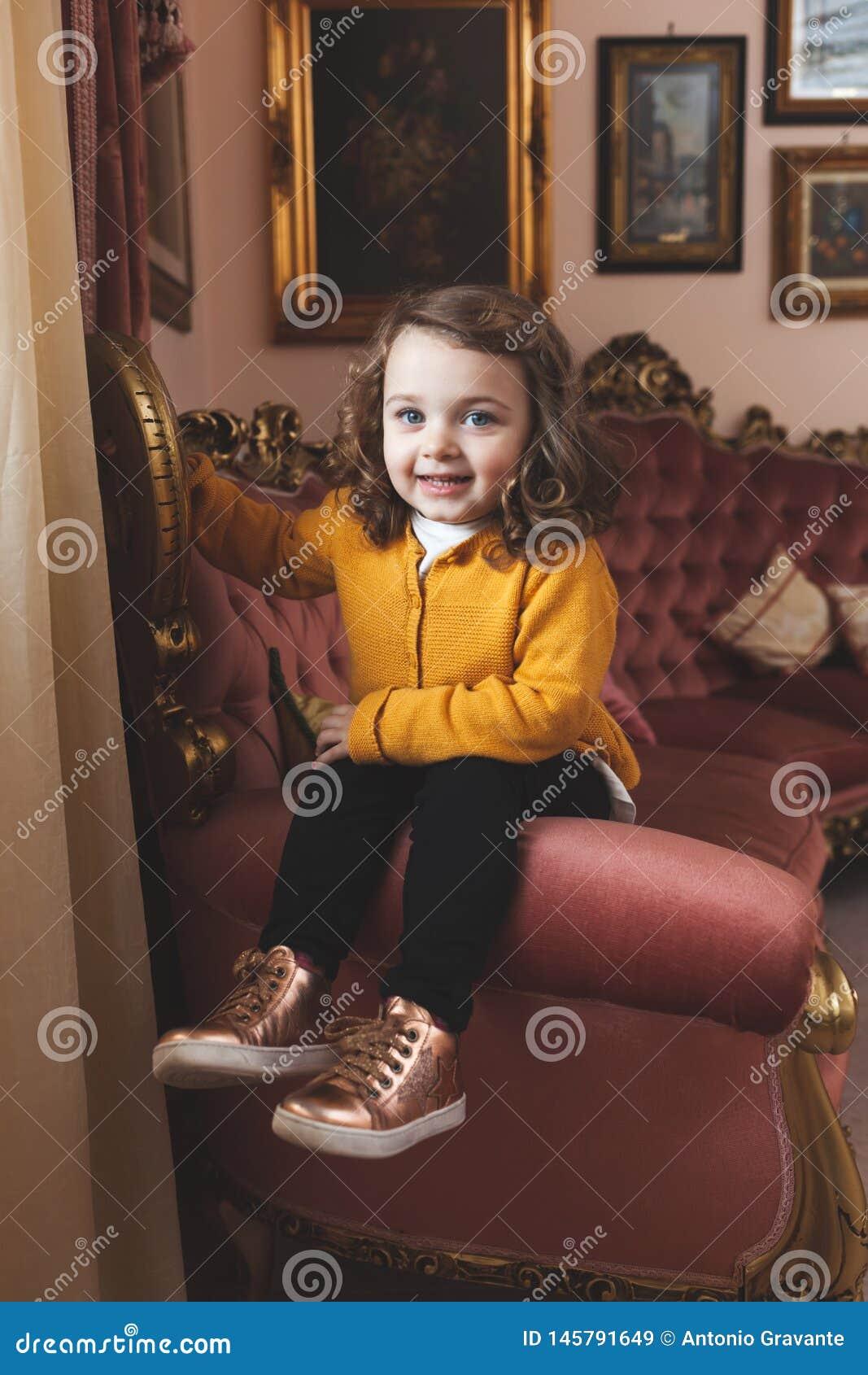 Crian?a da menina em uma sala de visitas com decora??o barroco