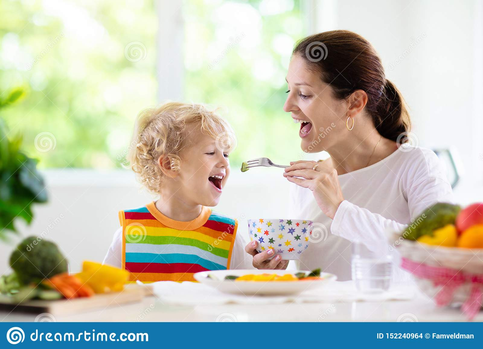 Crian?a de alimenta??o da matriz A mam? alimenta vegetais da crian?a