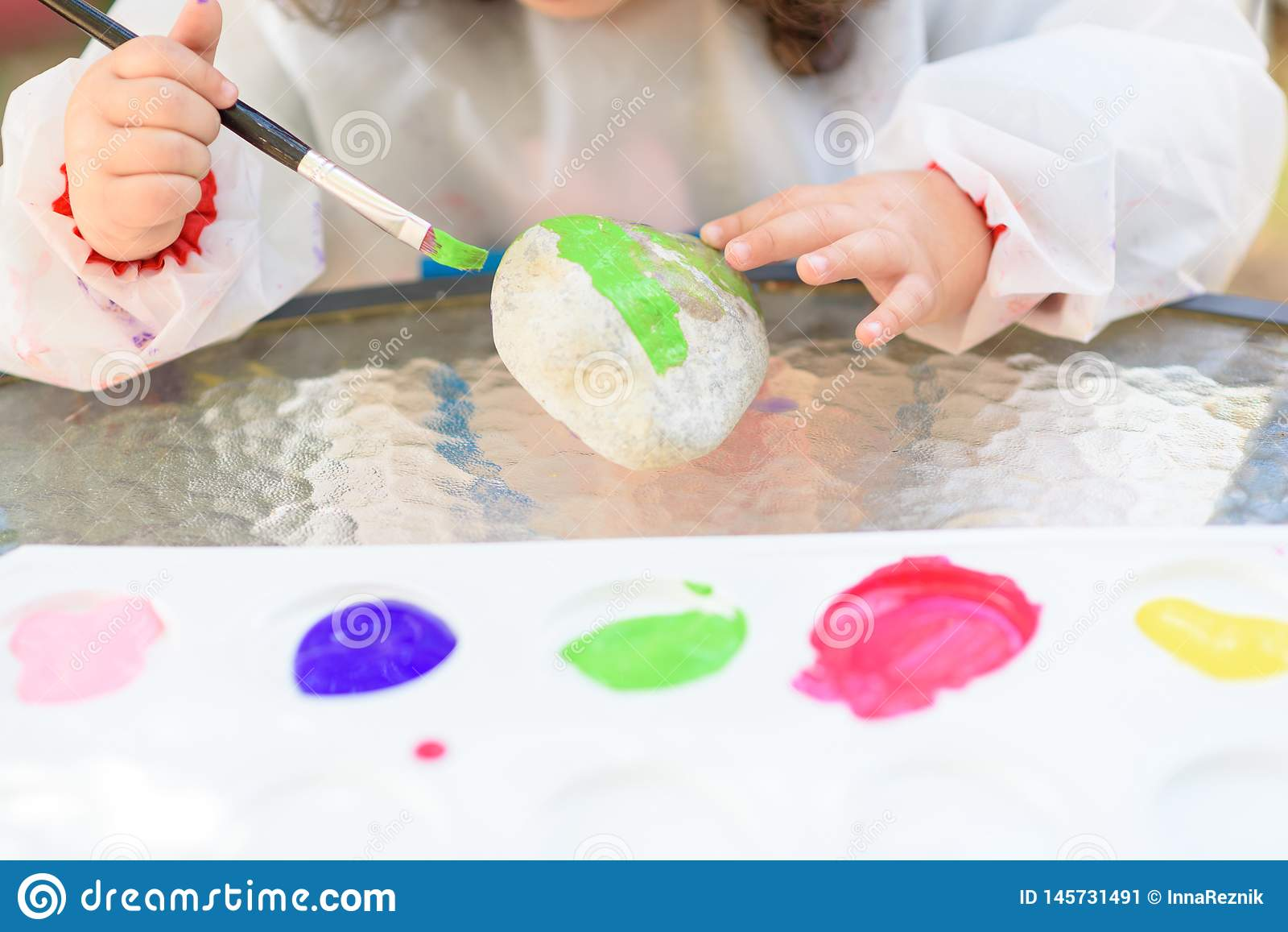 A crian?a do close-up entrega a pintura pelo pincel e pelas aquarelas