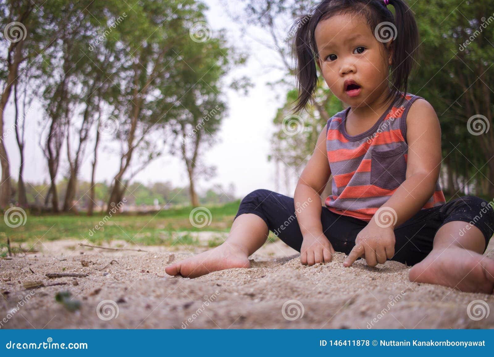 Crian?a feliz que joga com areia, fam?lia asi?tica engra?ada em um parque