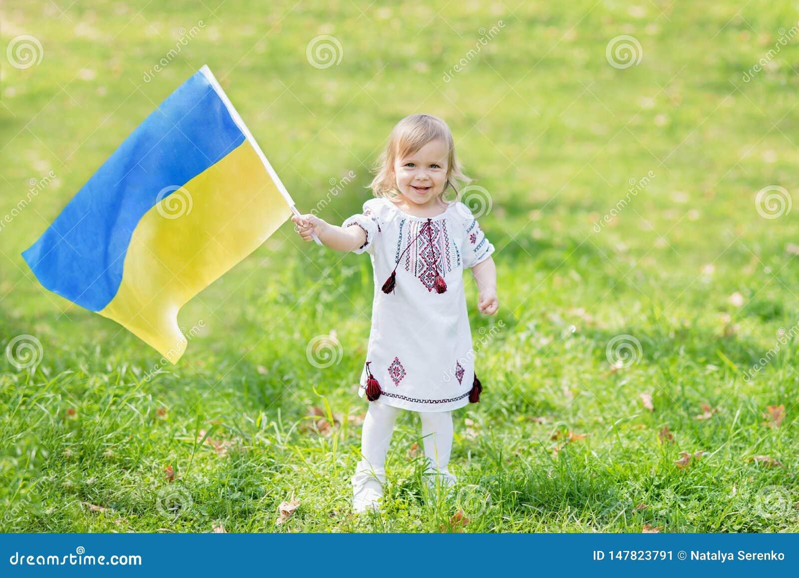 A crian?a leva a vibra??o bandeira azul e amarela de Ucr?nia no campo Dia da Independ?ncia do ` s de Ucr?nia Dia de bandeira Dia