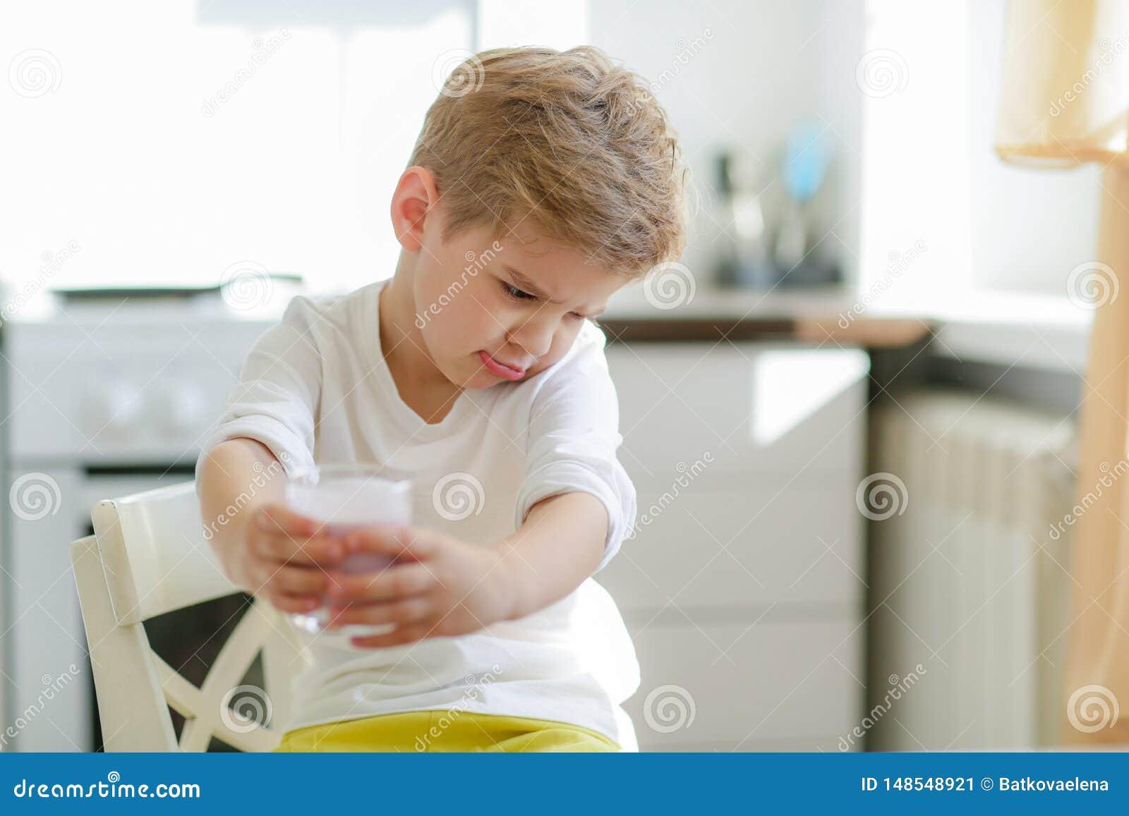 Crian?a ou menino feliz louro que comem na tabela Inf?ncia e felicidade, independ?ncia Caf? da manh?, manh?, fam?lia Menino peque