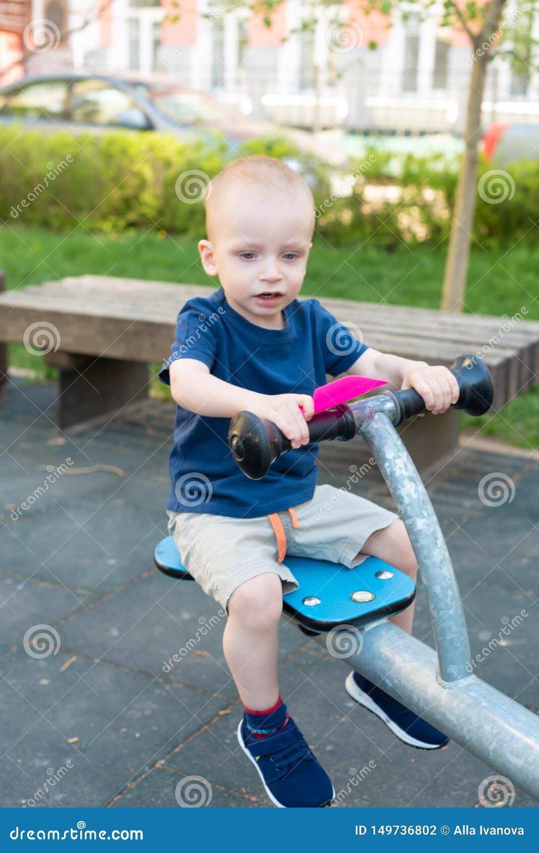 Crian?a que joga no campo de jogos exterior no ver?o As crian?as jogam na jarda do jardim de inf?ncia Crian?a ativa no balan?o co