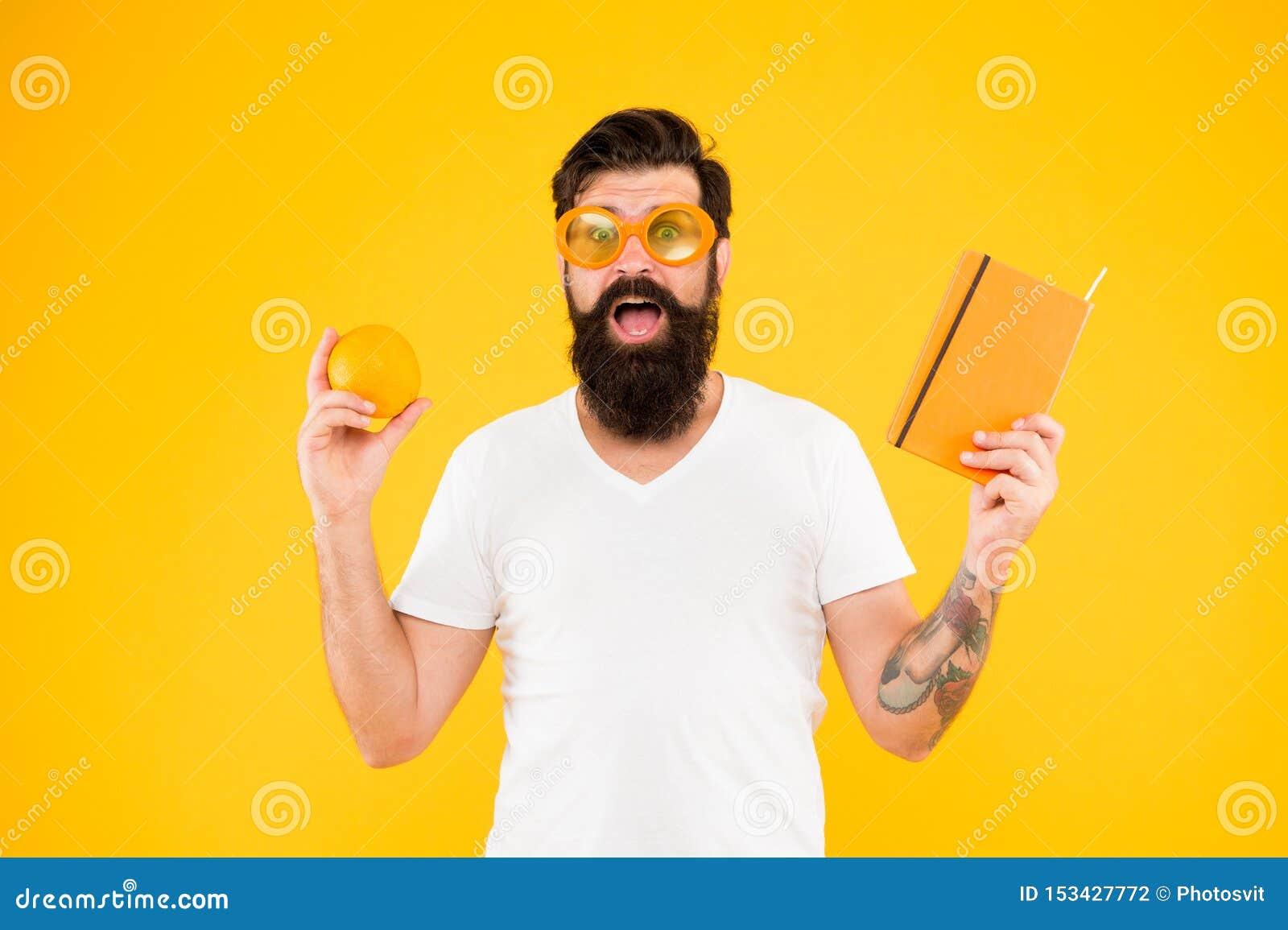 Criando uma dieta de leitura equilibrada Moderno que guarda o fruto e o livro alaranjados para ler no fundo amarelo Homem farpado