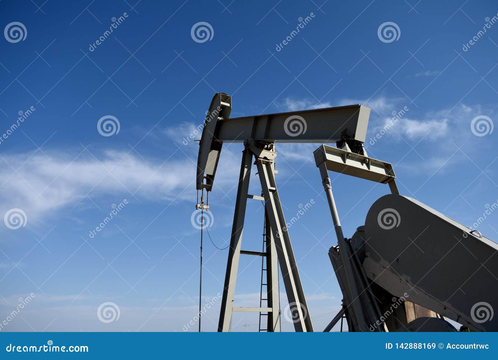 Cric de pompe de site de puits de production de pétrole brut contre les cieux bleus dans le schiste de Niobrara