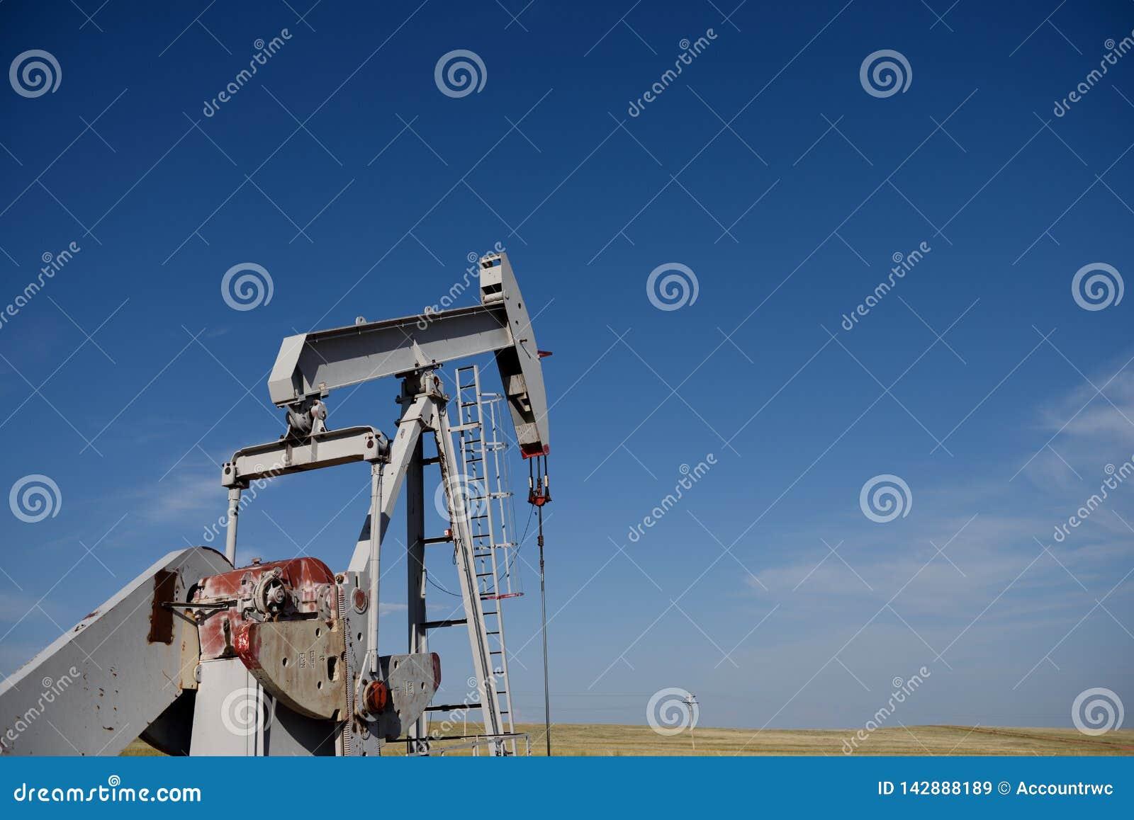 Cric et gisements de pompe de site de puits de production de pétrole brut contre les cieux bleus dans le schiste de Niobrara