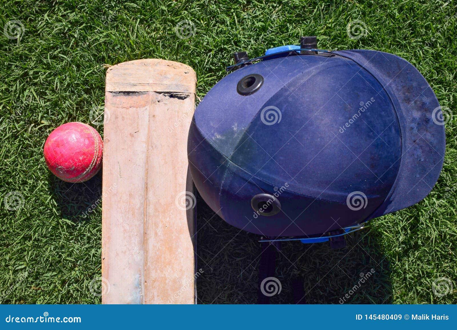 Cricket halmet ,bat, ball isolated on a green grass.