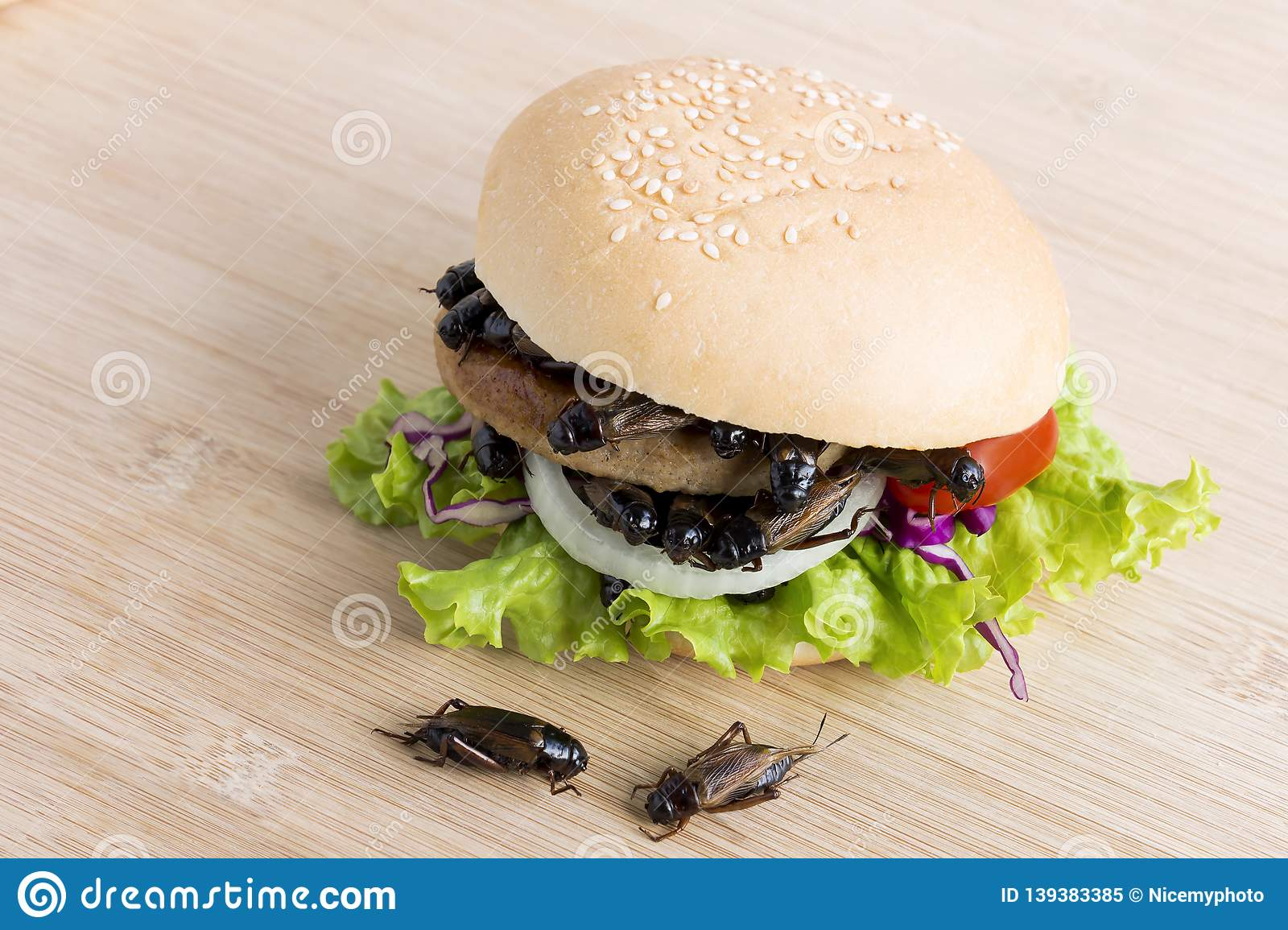 Crickets insect for eating as food items in bread burger made of fried insect meat with vegetable on wooden table it is good