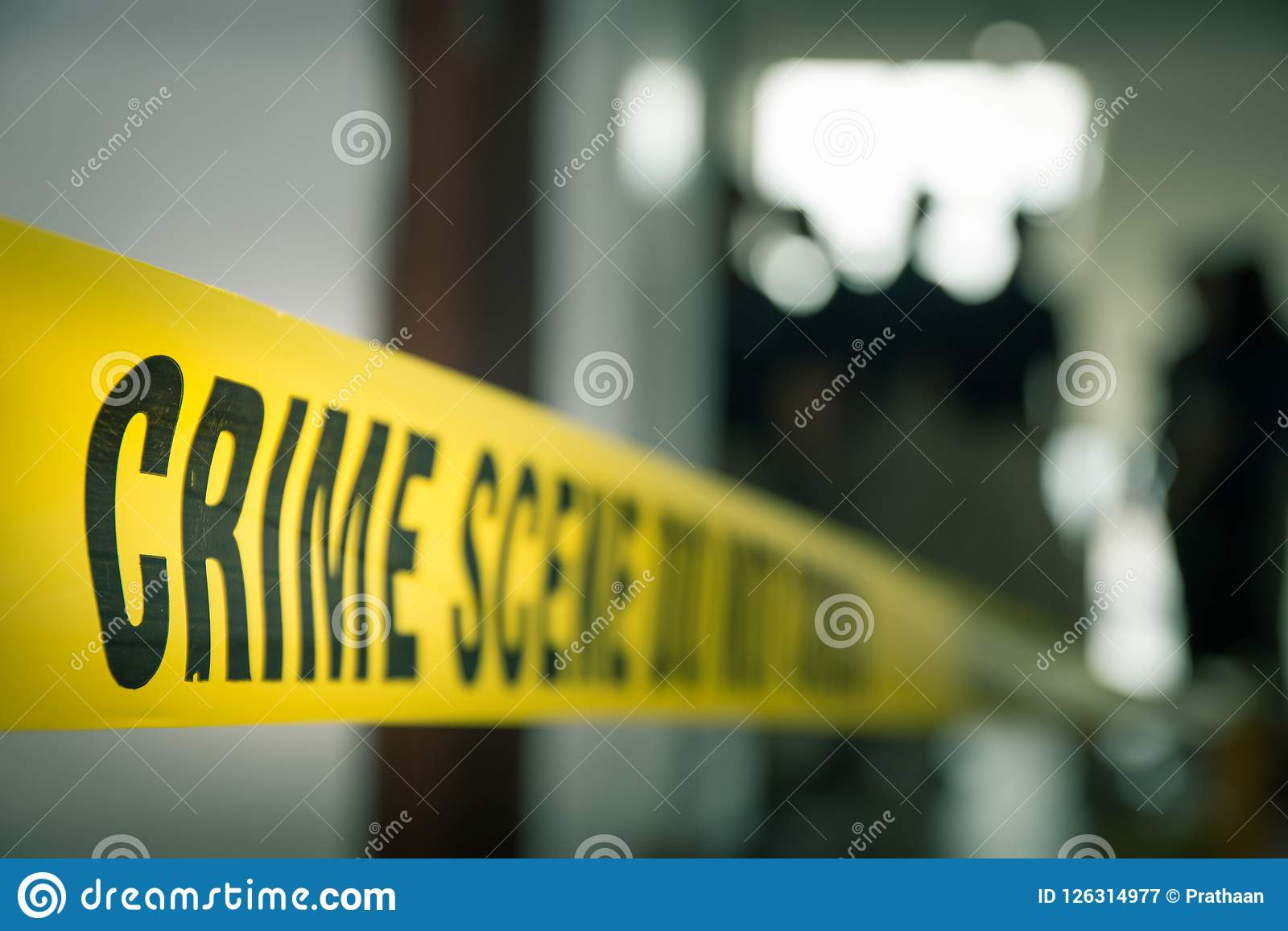 crime concept by police line tape with blurred forensic law enforcement background in cinematic tone