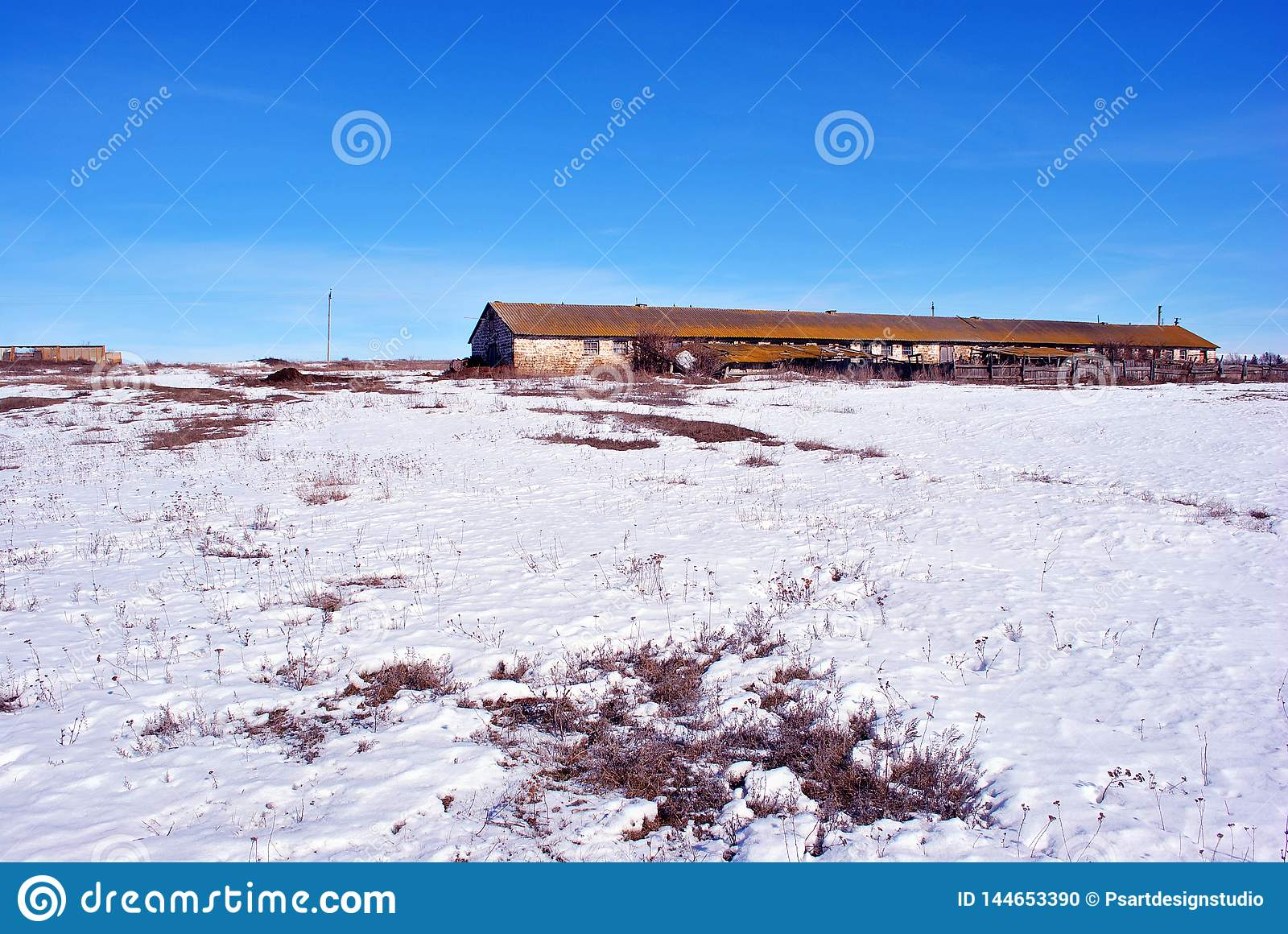 Crimean coquina rock blocks farm , dry weathered grass field covered with snow, blue clear sky