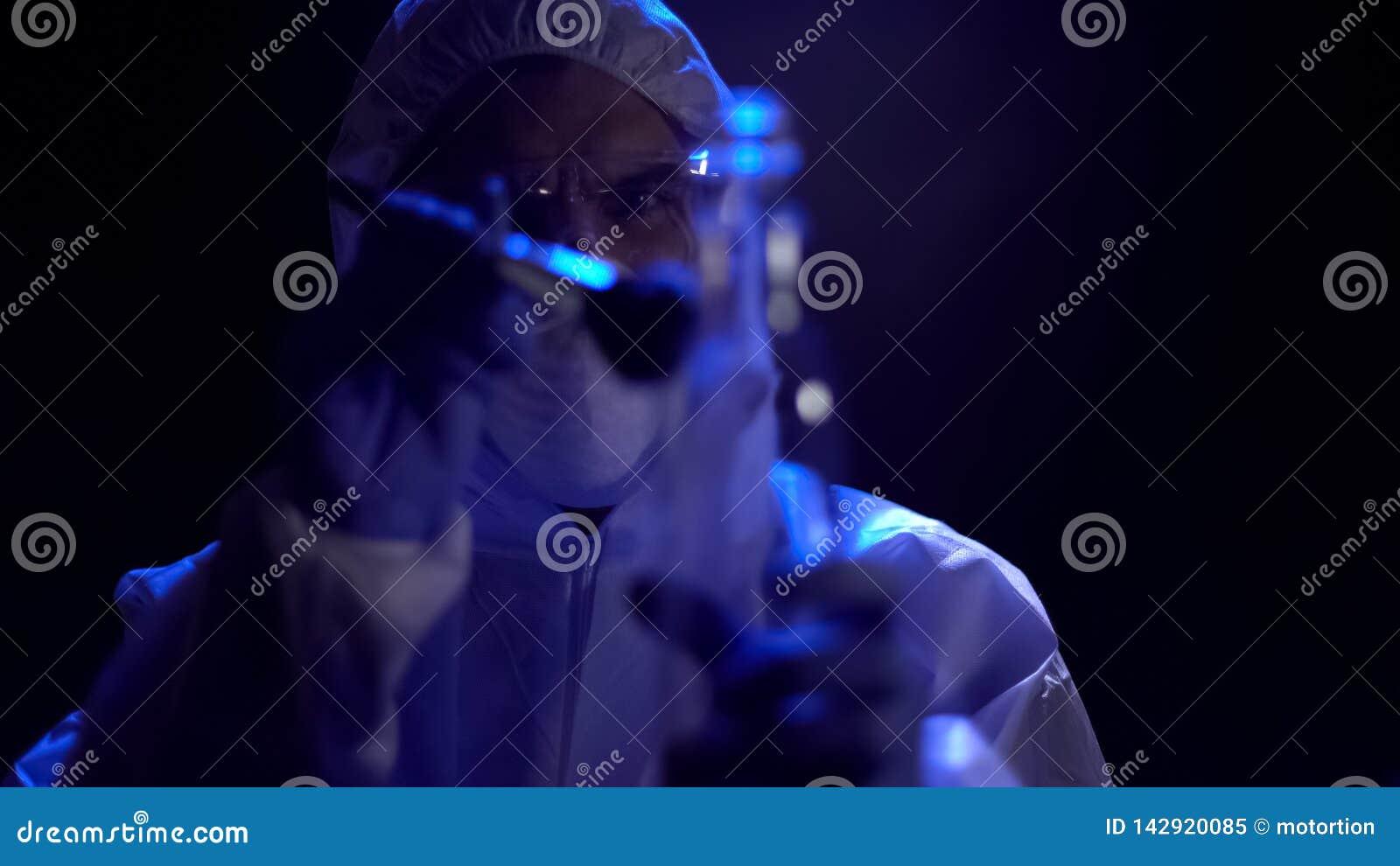 Criminalista que toma huellas dactilares de la botella en la escena del crimen, búsqueda para las pruebas