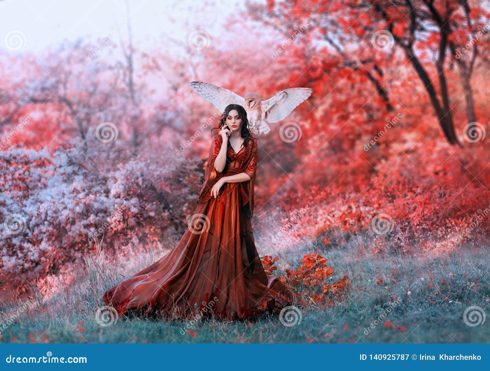 Crisalide potente di autunno, regina di fuoco e dea del sole caldo, signora in vestito lungo da luce rossa con le maniche sciolte