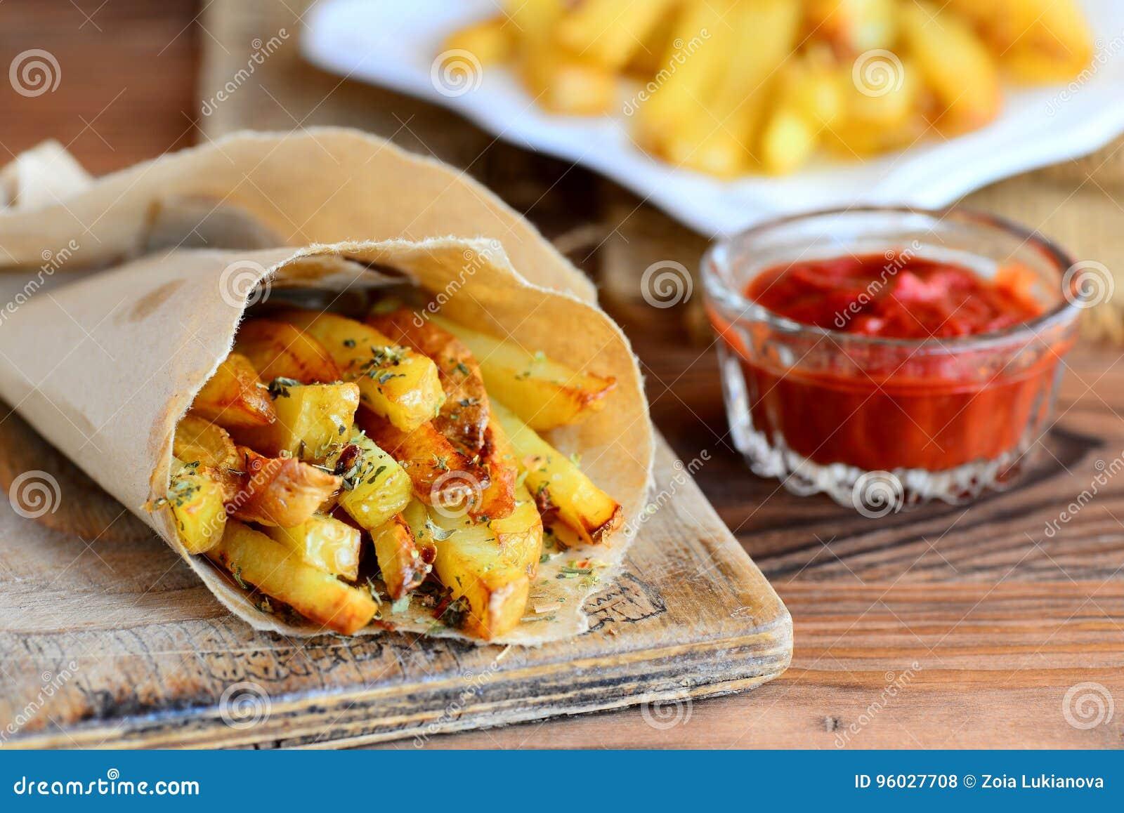 Crispy grula dłoniaki Piekarnik piec batat smaży w papierze i bielu talerzu, pomidorowy kumberland tabela drewna Wieśniaka styl z