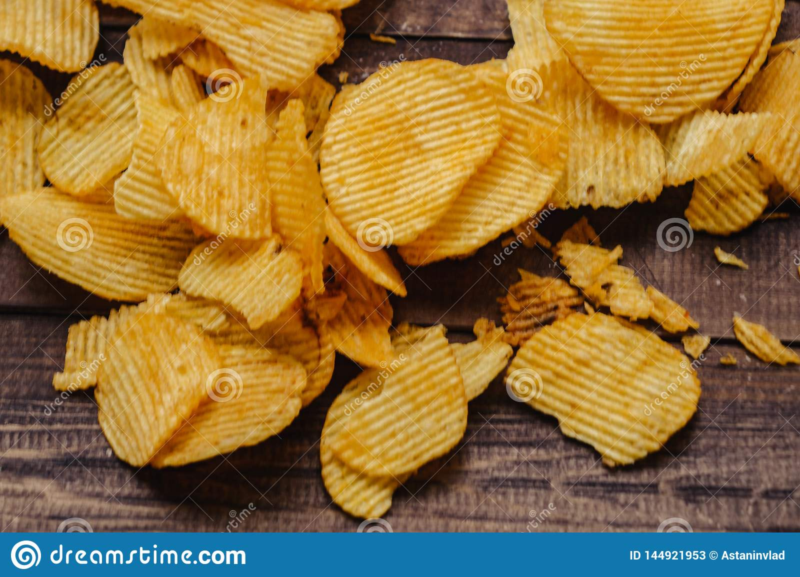 crispy potato chips on wooden background. chips started
