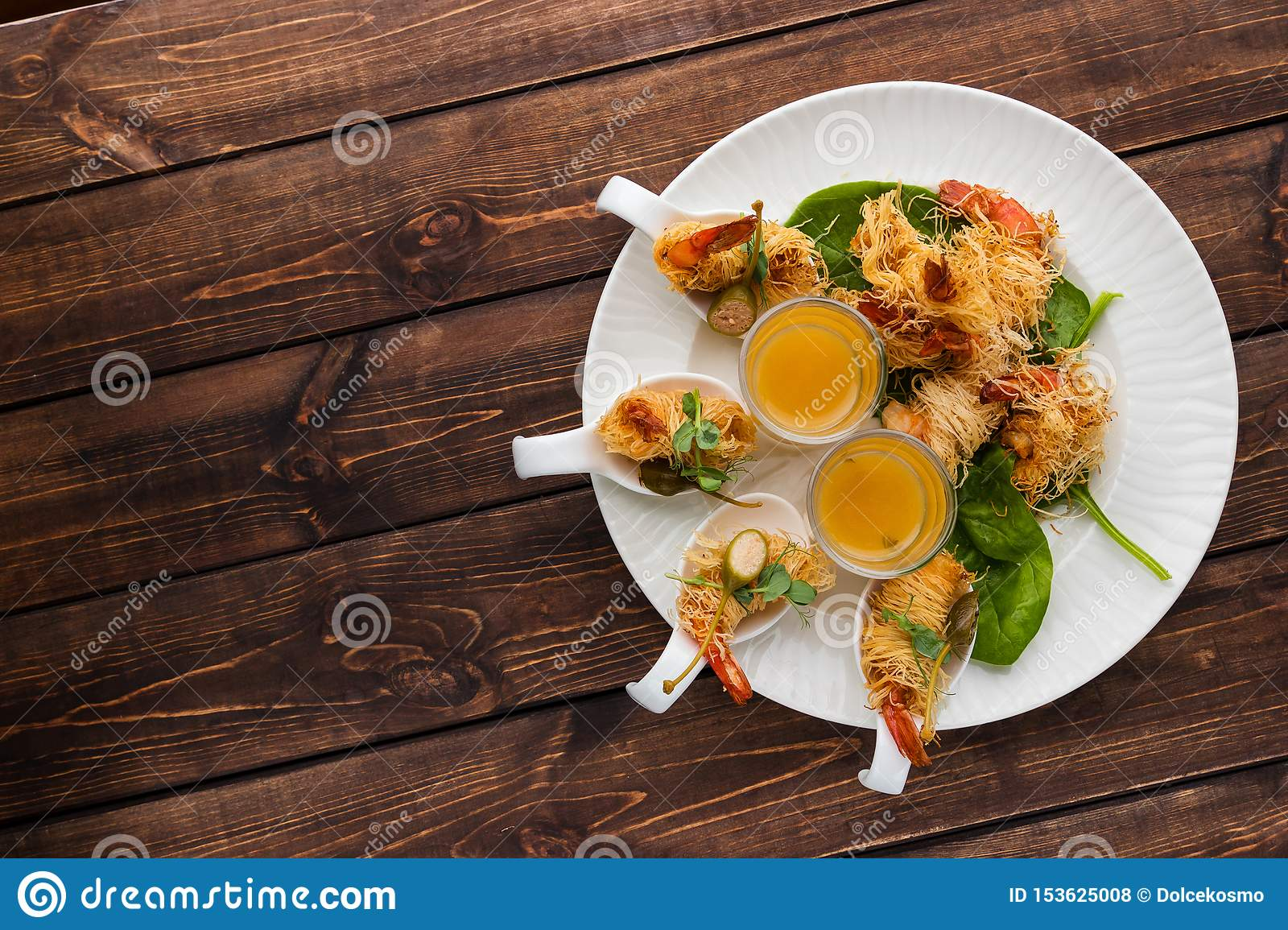 Crispy Shrimp in Kataifi Crust and Thyme with Champagne Sauce in glasses lie on a white plate on a woody background. Free space
