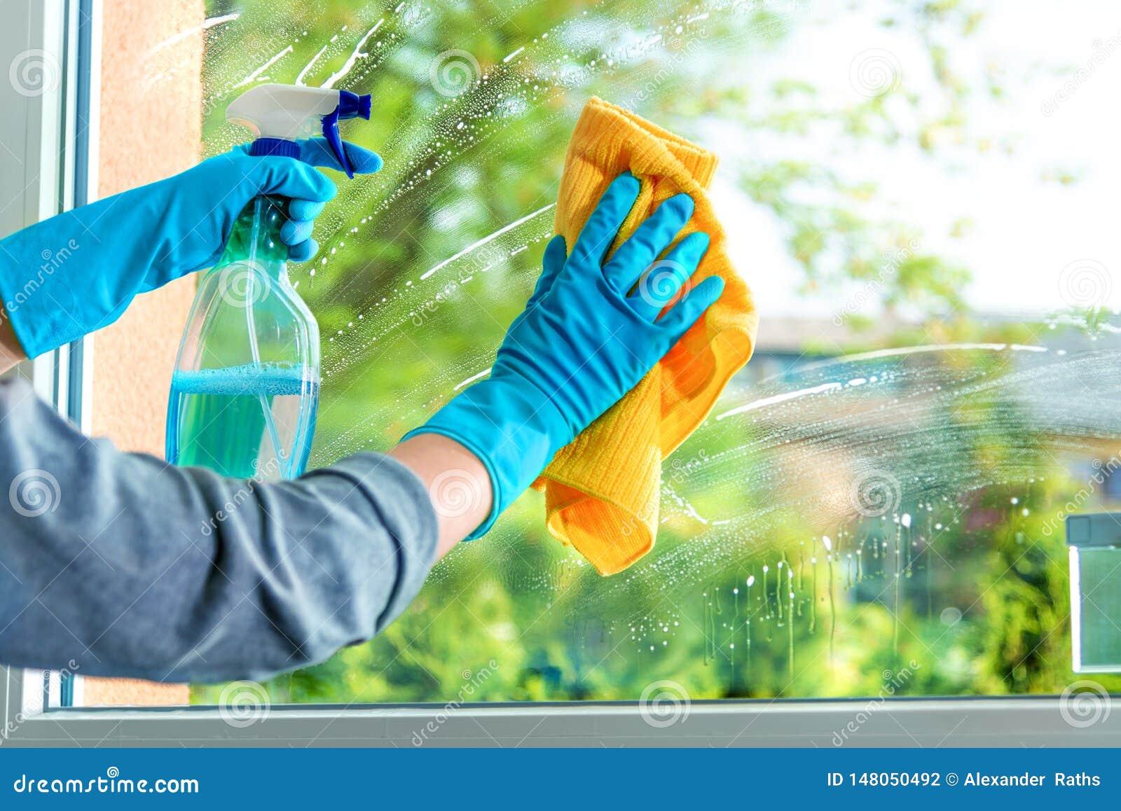 Cristal de ventana de la limpieza con el detergente