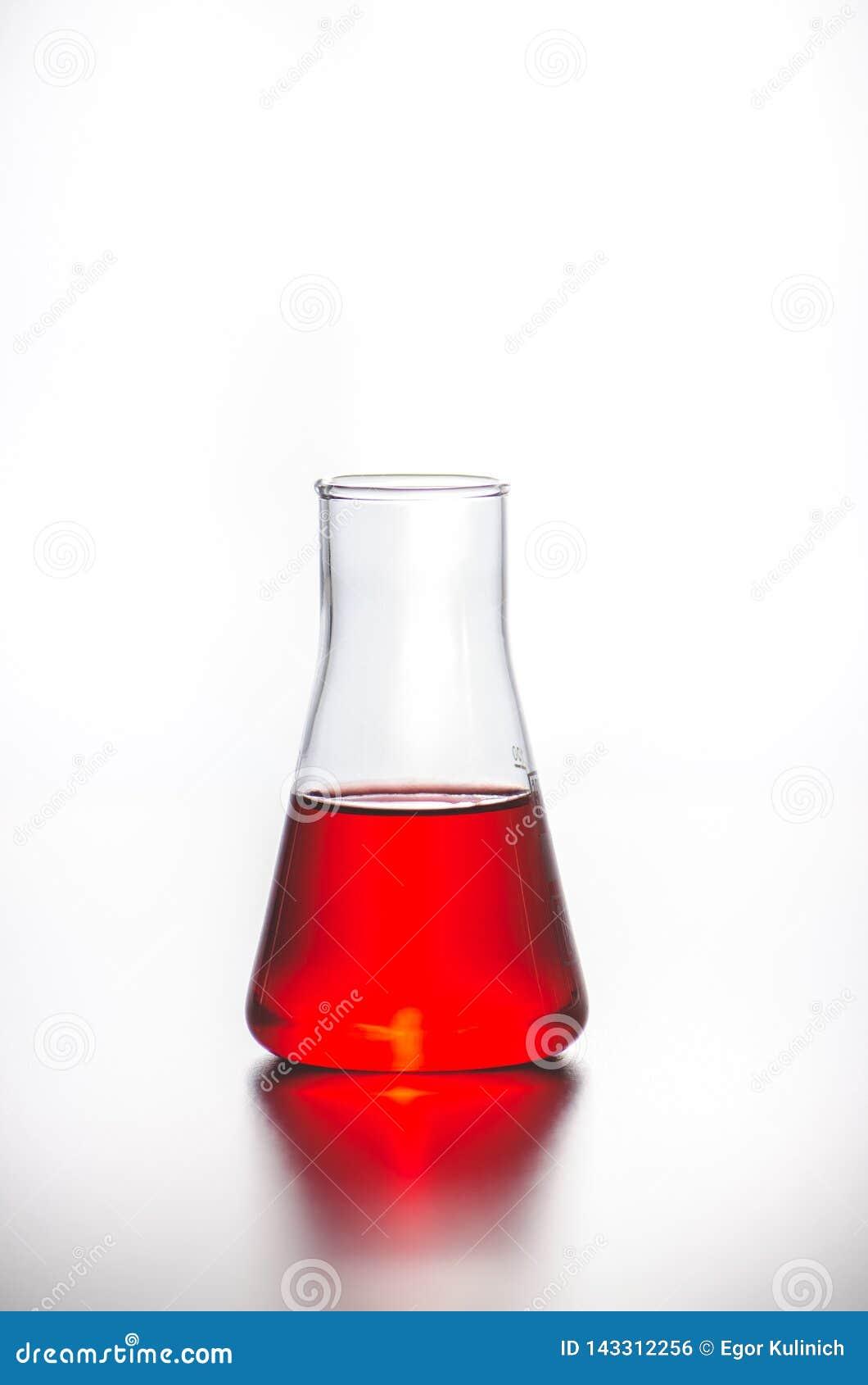 Cristalería Frasco con el líquido rojo en un fondo blanco Pruebas de laboratorio