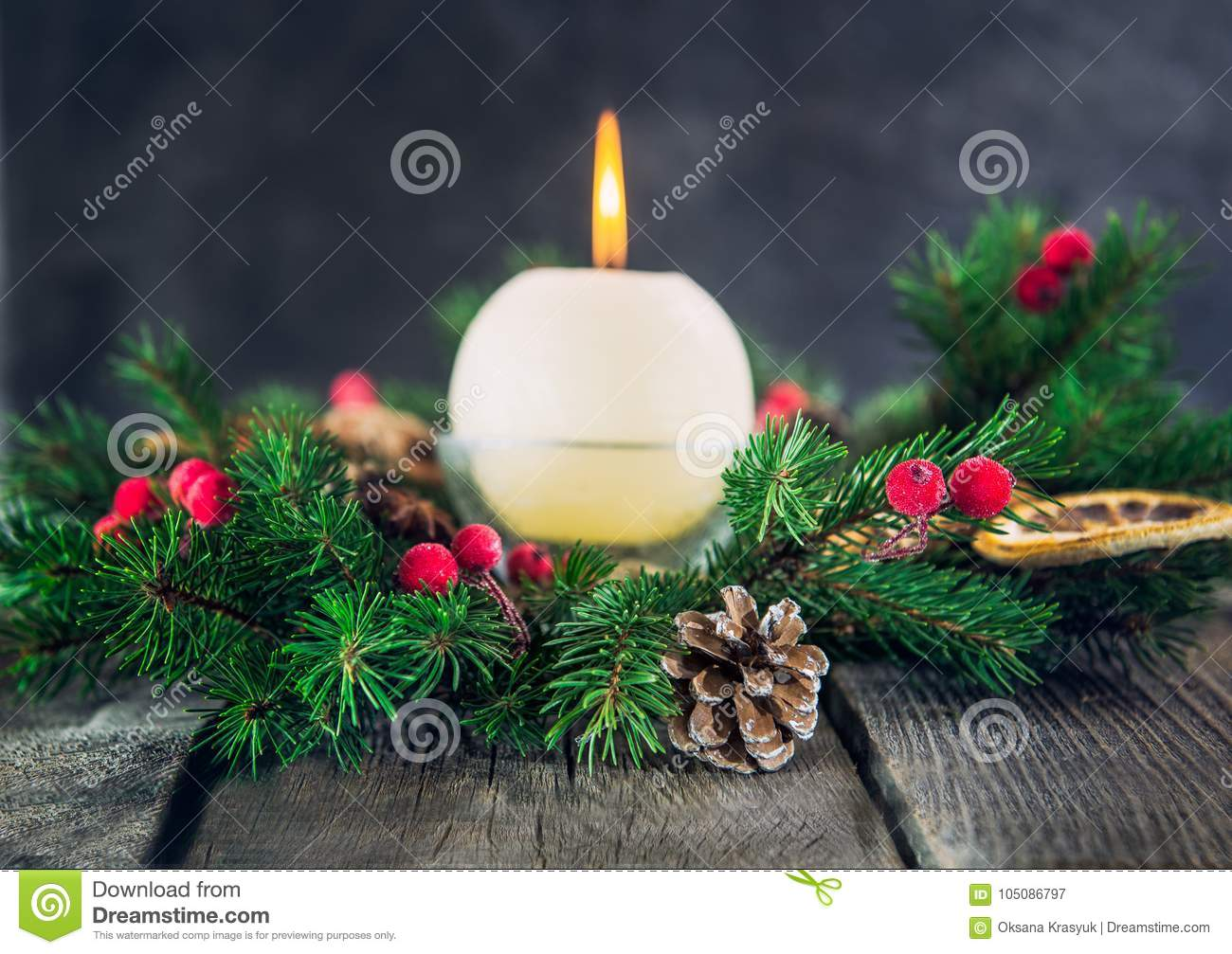 Cristmas card with focused fir cone and branches of advent wreath with natural decor and blurred burning candle on the old rustic