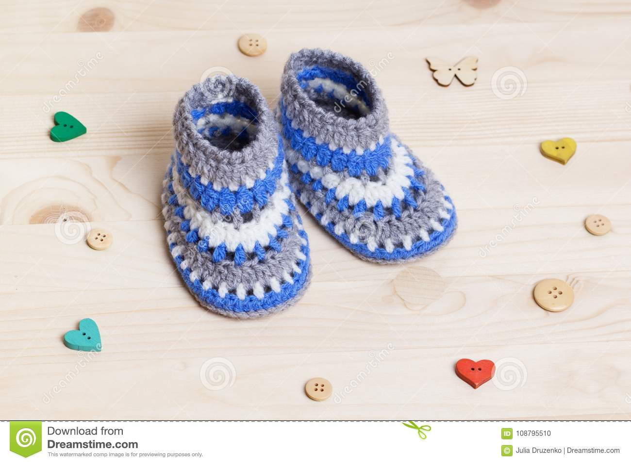 1c6ec3583354 Cute Handmade blue Baby Booties Crochet on wooden background with wooden  buttons