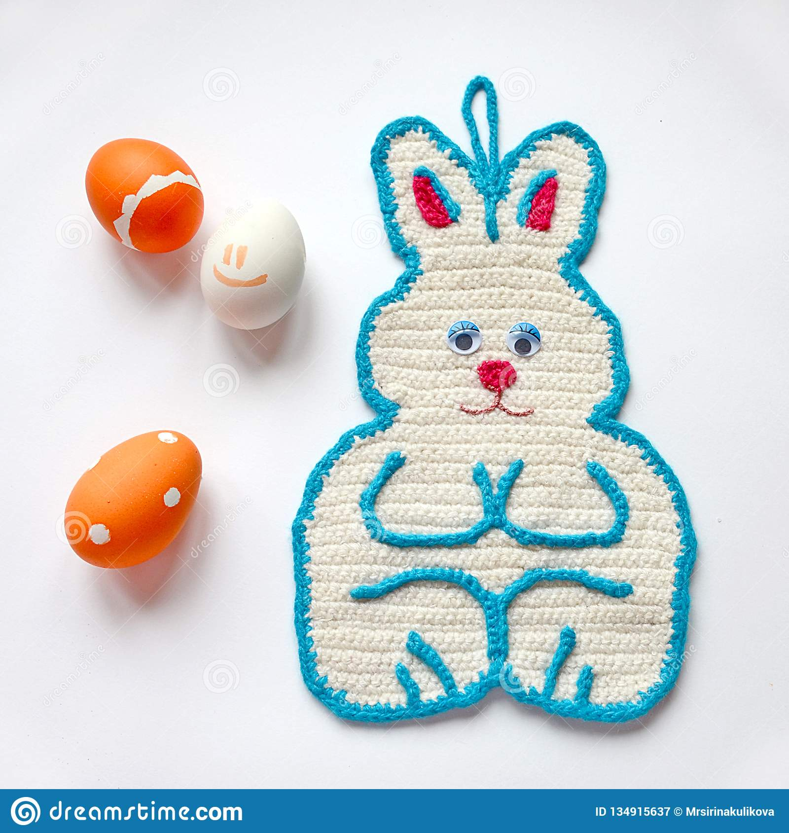 Crochet potholder Easter bunny white color with blue border and pink nose. Orange painted Easter eggs with patterns