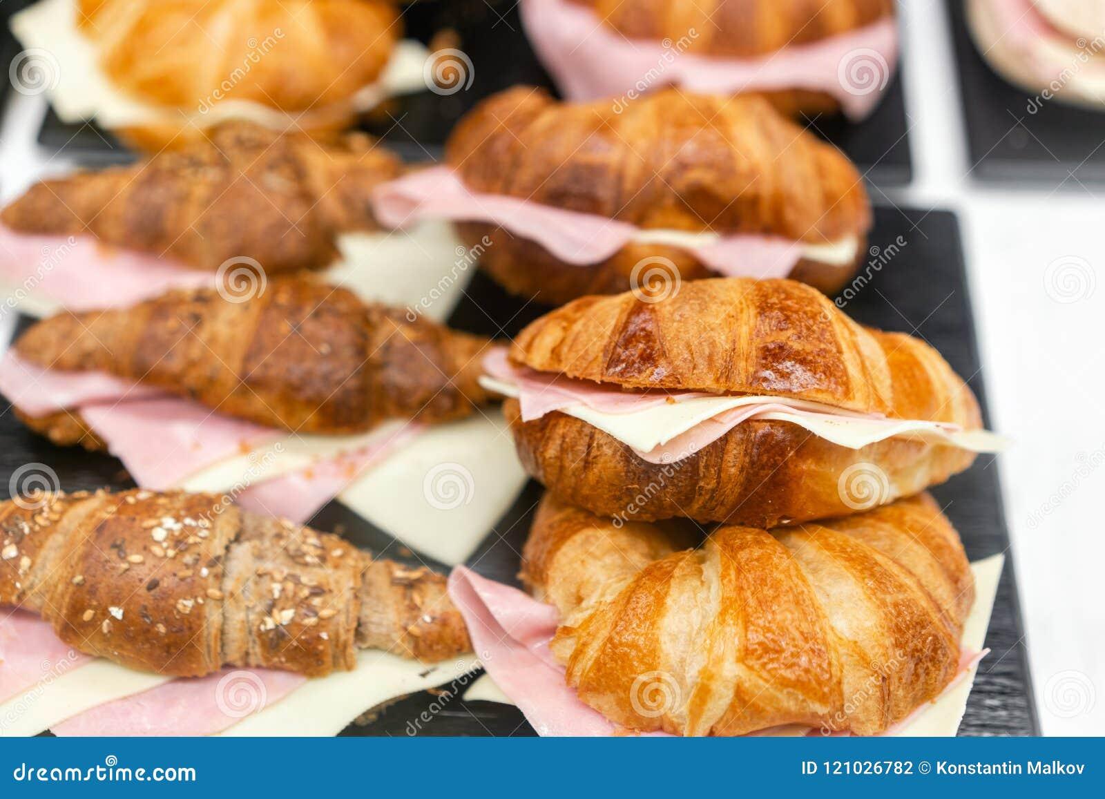 Croissant με το ζαμπόν και το τυρί Οι καυτές ζύμες βρίσκονται στο ράφι στον καφέ Κουλούρια και bagels στο κατάστημα