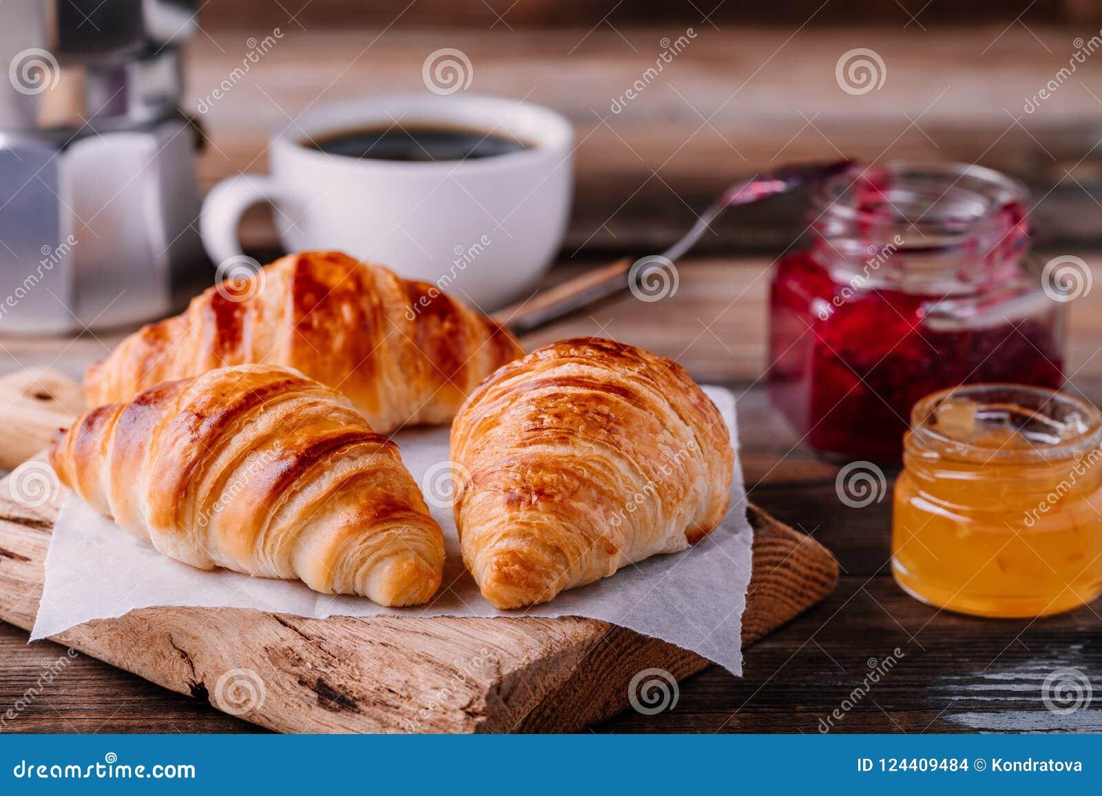 Croissant al forno casalinghi con inceppamento e caffè su fondo rustico di legno