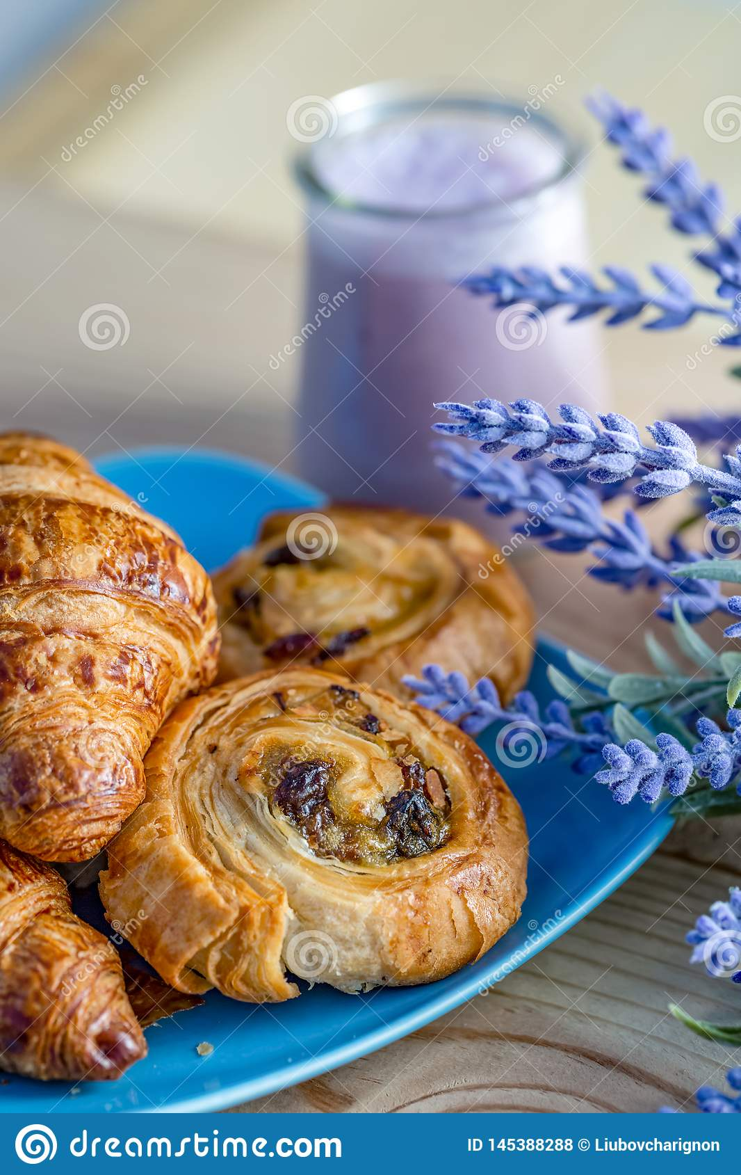 Croissant, bolos com passas em uma placa azul e iogurte de mirtilo no frasco de vidro