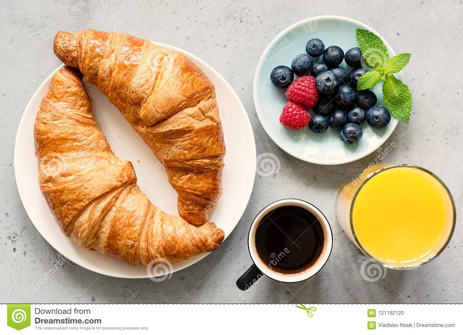 Croissant, café preto, suco de laranja e bagas frescas