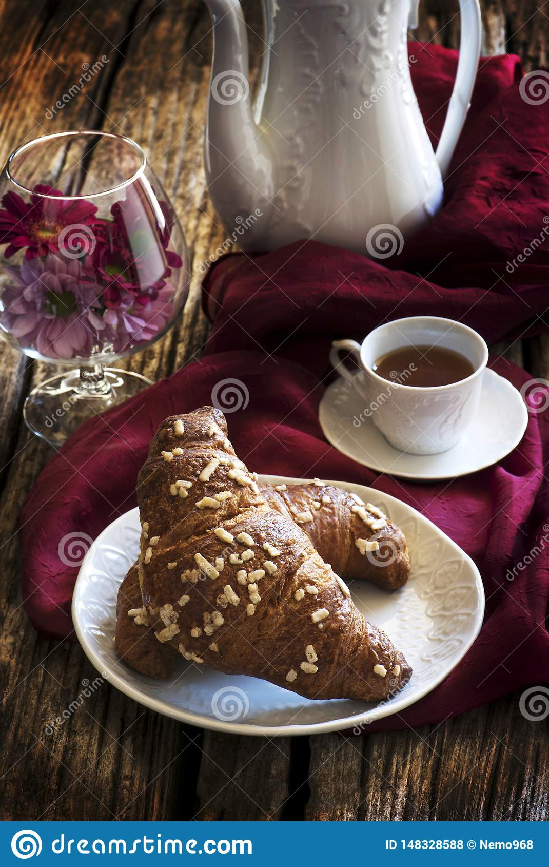 Croissant and coffee with coffee pot and plate