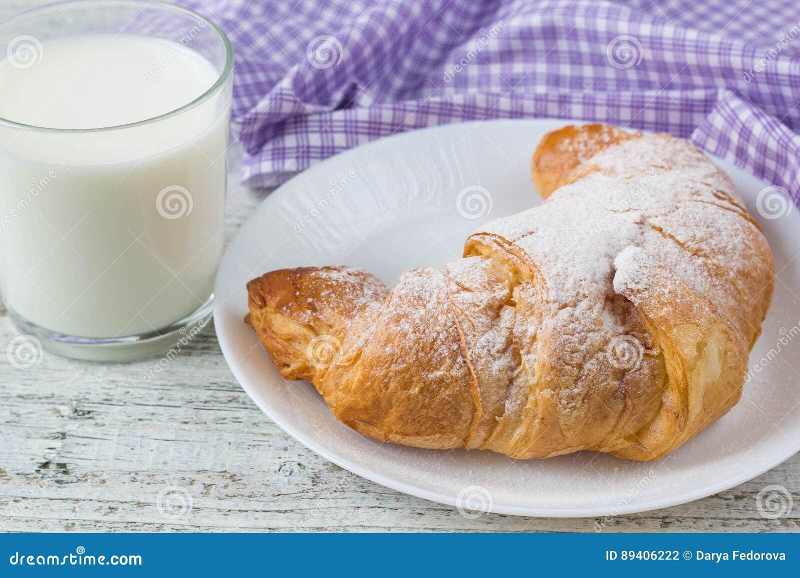 Croissant com leite na tabela de madeira velha para o fundo do café da manhã