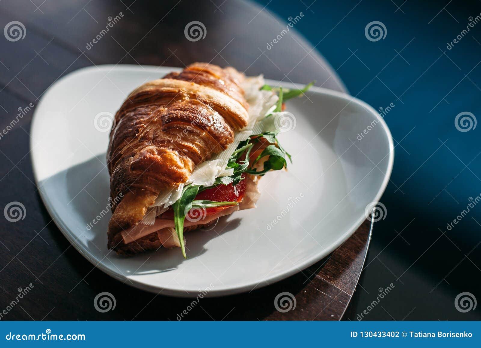 Croissant con il prosciutto ed il formaggio su una zolla