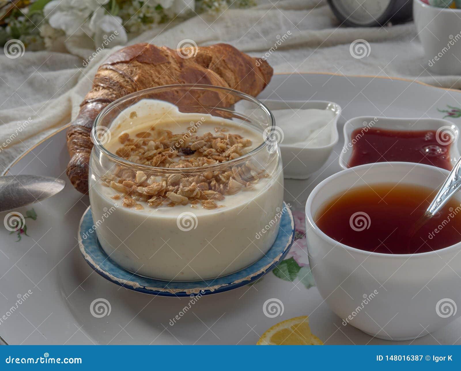 Croissant, doce, ch? com lim?o, em um prato de porcelana