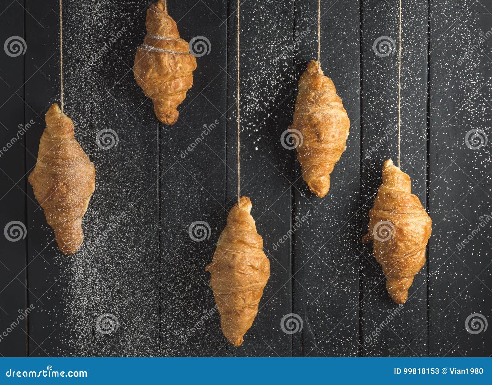 Croissant dorati su fondo di legno nero