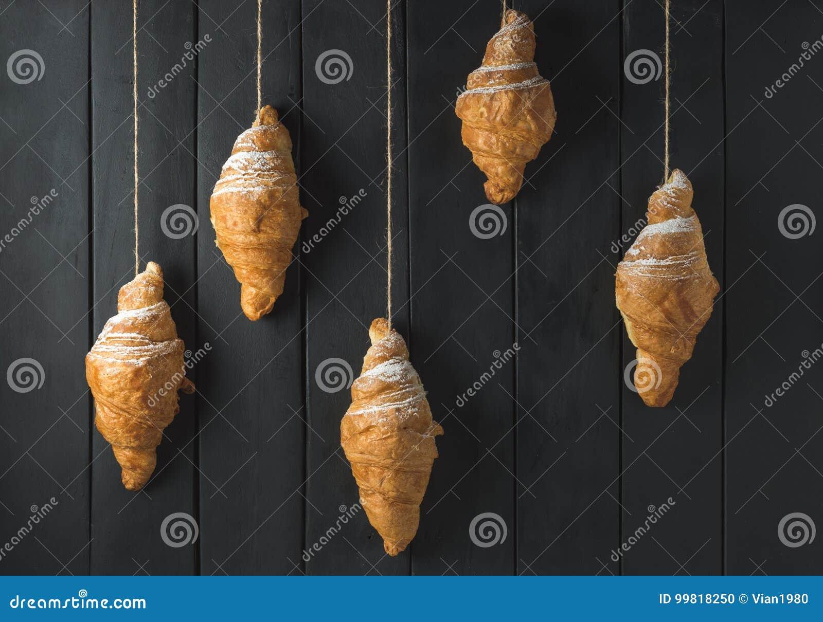Croissant dorati su fondo di legno nero rustico