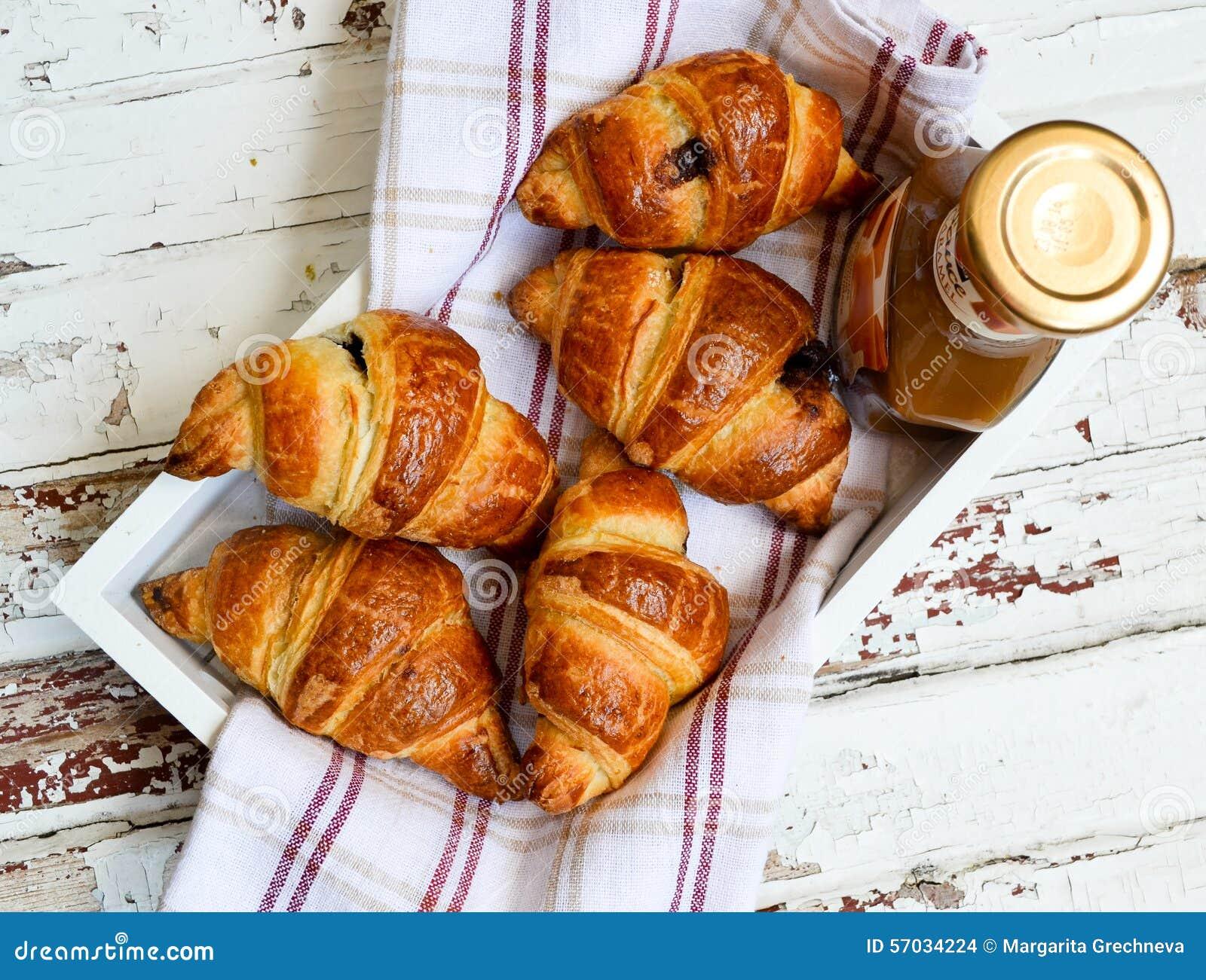 Croissant e caramelo na bandeja de madeira