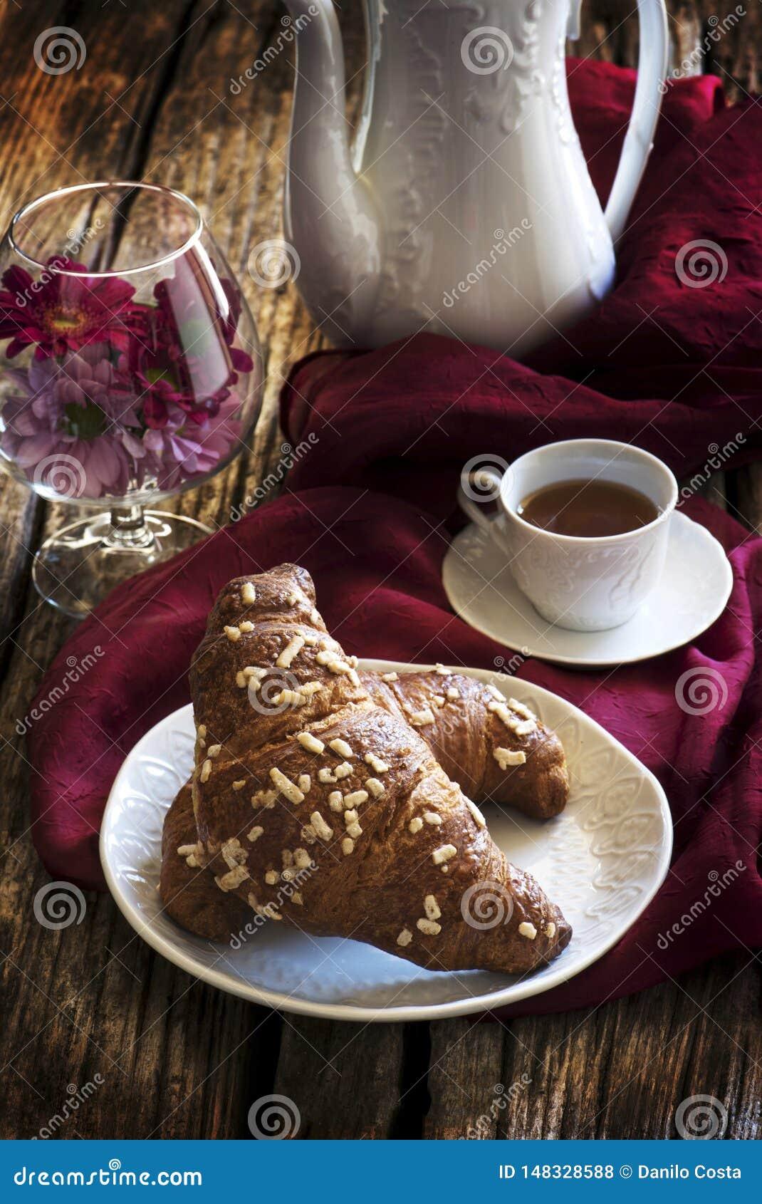 Croissant en koffie met koffiepot en plaat