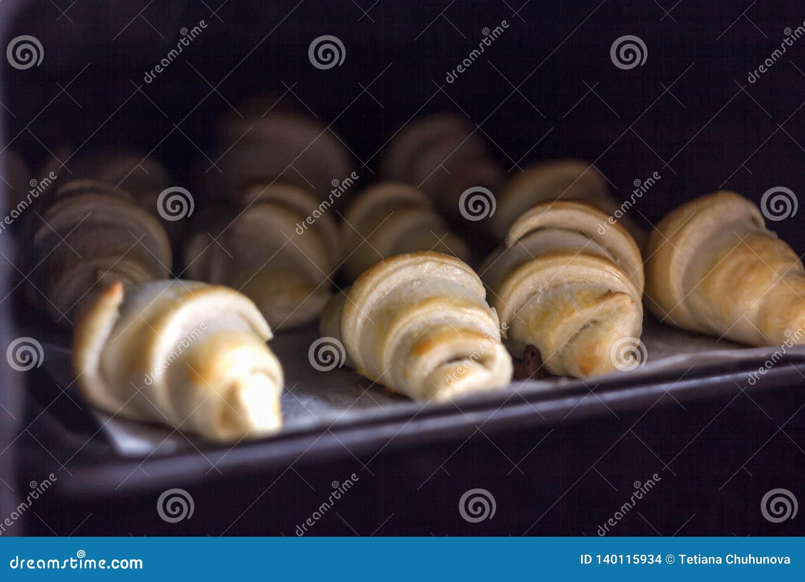 Croissant recentemente cozidos com chocolate em uma bandeja de cozimento no forno
