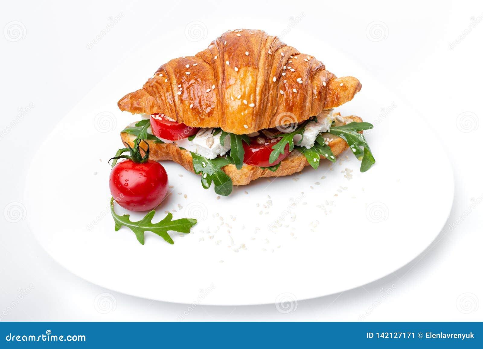 Croissant saboroso com tomate e ruccola na placa do whie