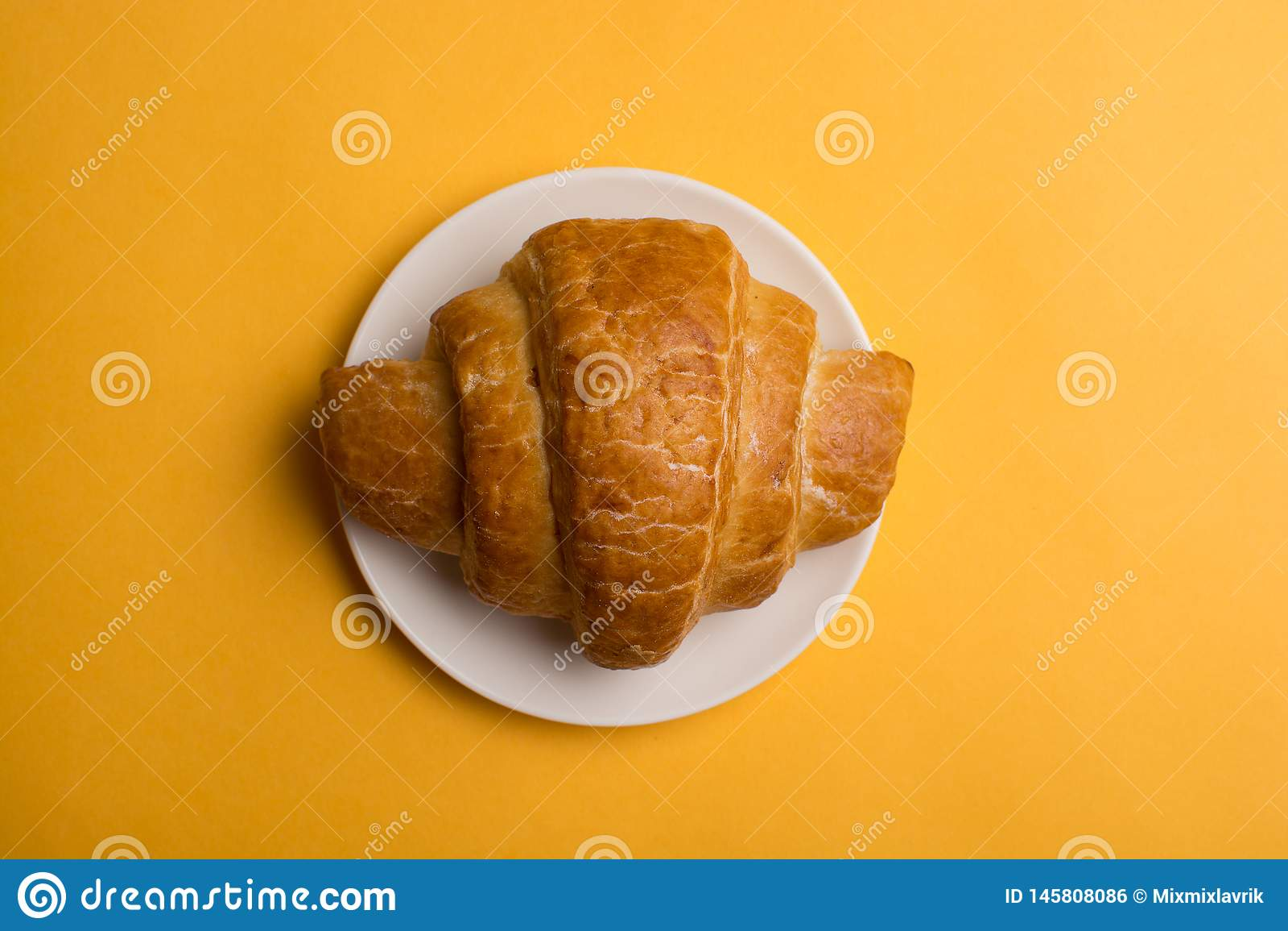 Croissants σε ένα άσπρο πιάτο σε ένα κίτρινο υπόβαθρο