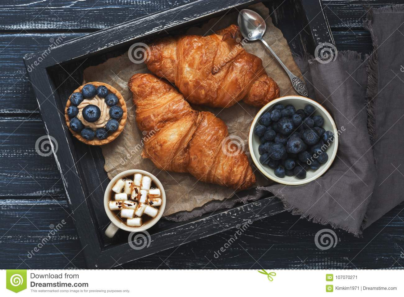 Croissants, cake with blueberries, coffee with marshmallows on a wooden tray with a napkin. Wooden dark background, top view.