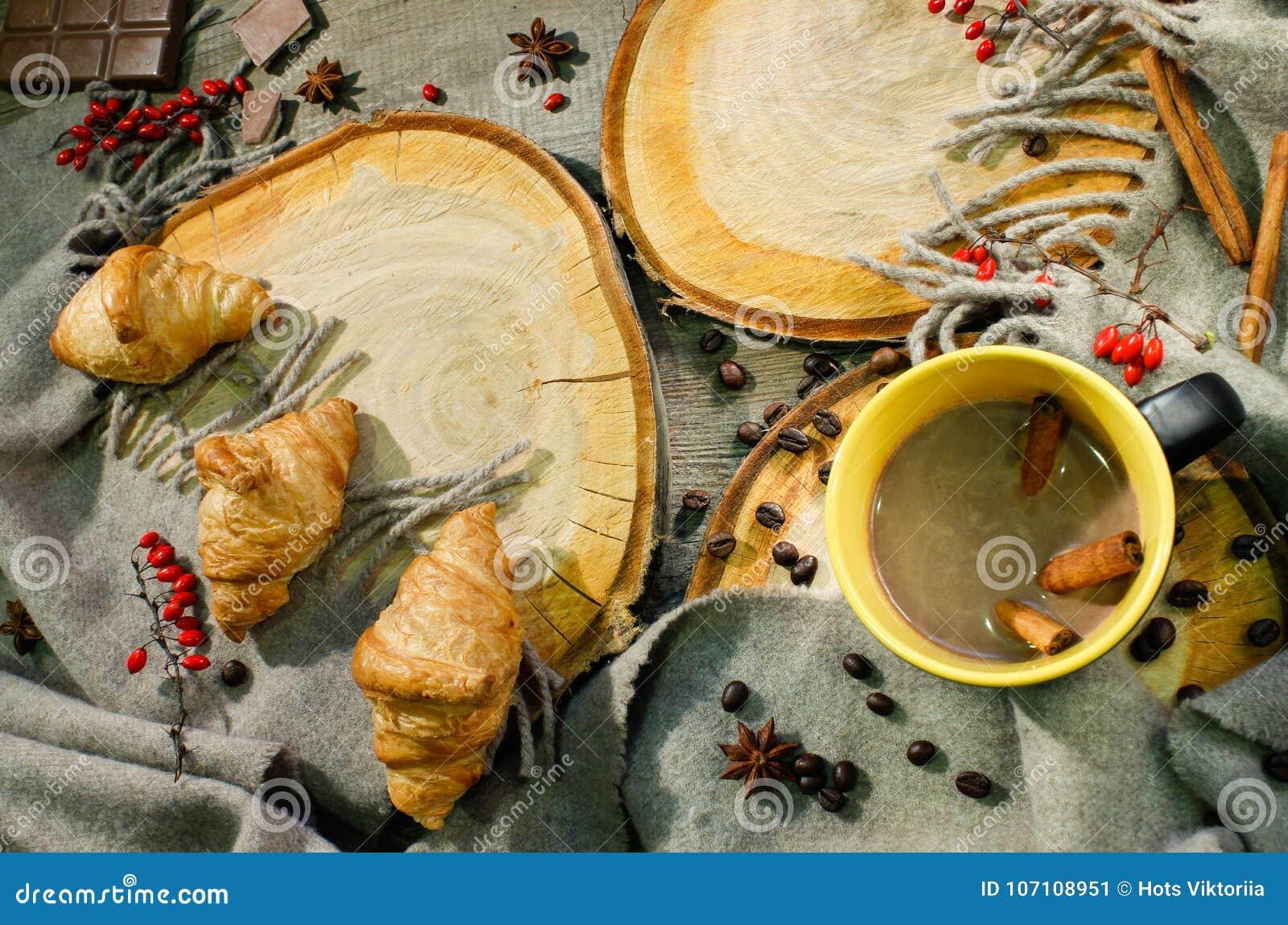 Croissants i filiżanka kawy na drewnianej powierzchni wśród woolen jagod powszechnych i czerwonych Jesień motyw